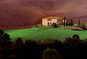 With the fields plowed in the background the farmhouse and grassy area glow in the changing Tuscan light.