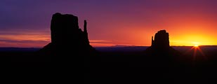 The Mittens at Monument Valley backlit at sundown.